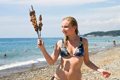 Girl with barbecue. On the beach Stock Images