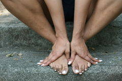 Girl bare feet. Girl sitting down with hands on her bare feet royalty free stock photos