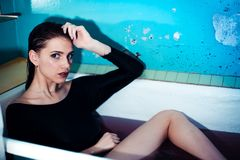 Girl with bare shoulders lying in the bathroom with colored purple water. Fashion concept stock photos