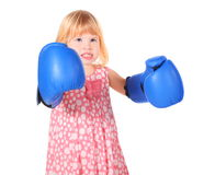 Girl with bared teeth and boxers gloves. Little girl with bared teeth wearing dress and boxers gloves is standing. isolated Royalty Free Stock Photos