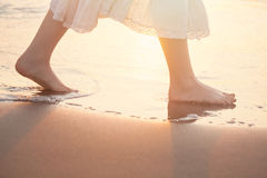Girl Barefoot are Walking on the Beach in Water. Vacation in Summer at the Sea Royalty Free Stock Photography