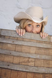 Girl in a Barrel. Young cowgirl peeking out of a barrel with a humorous expression on her face stock photo