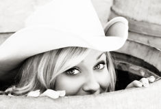 Girl in a Barrel. Young cowgirl peeking out of a barrel with a smile on her face Stock Photos