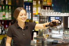 Girl bartender pours wine into a wine glass. A barman girl standing smiling, pours white wine into a glass from a bottle. Shelves with bottles of alcohol in the Stock Photos