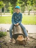 The girl in the baseball cap and denim clothes riding on the shape of the cochlea. Royalty Free Stock Photos