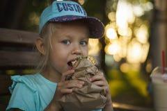 Girl in a baseball cap eating royalty free stock photos