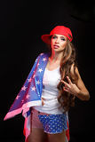 Girl in a baseball cap holding a flag of the USA Royalty Free Stock Photo