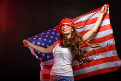 Girl in a baseball cap holding a US flag Royalty Free Stock Photo