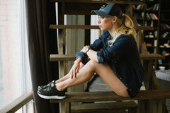 Girl in baseball cap. Sports girl in a baseball cap, black shorts and a denim jacket sits near the window on the stairs Royalty Free Stock Image