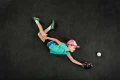 Girl baseball player making a diving catch Stock Images