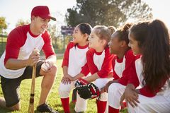 Girl baseball team kneeling in a huddle with their coach stock photos