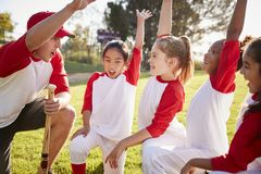 Girl baseball team kneeling with their coach, raising hands royalty free stock image