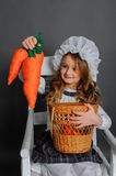 Girl with a basket and carrots on a gray background Stock Images