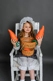 Girl with a basket and carrots on a gray background.  Stock Photography