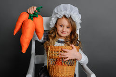 Girl with a basket and carrots on a gray background.  Royalty Free Stock Photo