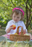 Girl with basket eating peach Stock Image