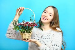 Girl with a basket of flowers. Beautiful smiling girl with a basket of flowers on a blue background Stock Photo