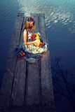 Girl with basket of flowers near a lake. Summer mood,the romanti Stock Photos