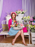 Girl with a basket of flowers sitting on a bench Stock Photography