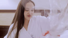 Girl with a basket of flowers. A girl in a white robe, sitting on the bed and unpacking flowers stock footage