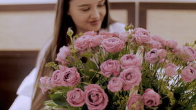 Girl with a basket of flowers. A girl in a white robe, sitting on the bed and unpacking flowers stock video