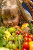 Girl with basket of fruit and vegetables. A cute young girl with a large basket of fruit and vegetables Stock Image