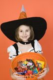 Girl With Basket Full Of Candies In Halloween Outfit Stock Photos