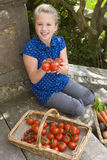 Girl (9-11) with basket of tomatoes, smiling, portrait Royalty Free Stock Image