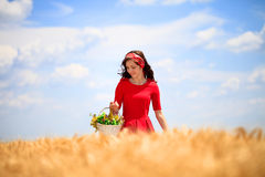 Girl with basket in wheat field Royalty Free Stock Image