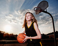 Girl with Basketball and Hoop Royalty Free Stock Image