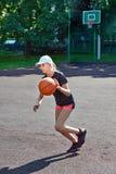 Girl basketball player running with ball. On street playground Stock Photos