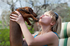 Girl with a Basset Hound. Girl playing with a dog dachshund outdoors Stock Photography