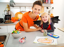 Girl in bat costume with mother creating halloween decorations Royalty Free Stock Image