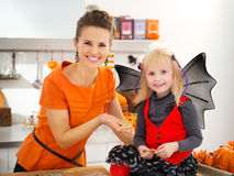 Girl in bat costume with mother holding Halloween cookies Stock Photography