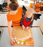 Girl in bat costume with mother making Halloween biscuits Stock Photos