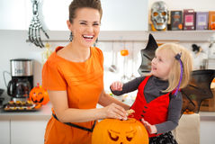 Girl in bat costume with mother preparing Jack-O-Lantern Stock Photo