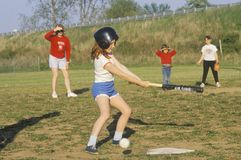 Girl at bat at Girls Baseball game Stock Images