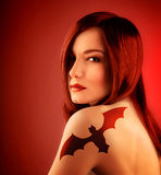 Girl with bat tatoo. Photo of beautiful sexy girl with bat tatoo on shoulder  on red background, halloween holiday decoration, seductive female with red hair Stock Photos