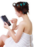 Girl in a bath towel and hair curlers with tablet computer in her hands. Royalty Free Stock Image