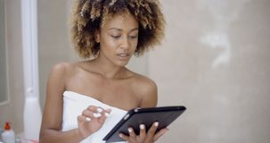 Girl In Bath Towels Using Touchpad. Girl in bath robe with touchpad networking in bathroom stock video