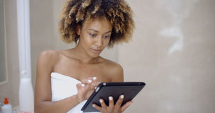 Girl In Bath Towels Using Touchpad Stock Photos