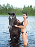 Girl bathe horse in a river Stock Image