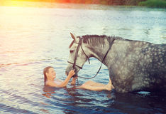 Girl bathe horse in a river Royalty Free Stock Photos