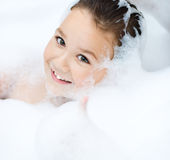 Girl bathes in a bathroom Stock Images