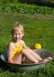 Girl bathes in a bucket Royalty Free Stock Photos