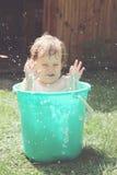 Girl bathes in a bucket Stock Photos