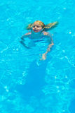 Girl bathes. In pool in blue clear water Stock Photos