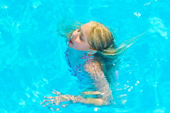 Girl bathes. In pool in blue clear water Stock Images