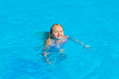 Girl bathes. In pool in blue clear water Royalty Free Stock Photo