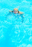 Girl bathes. In pool in blue clear water Royalty Free Stock Images